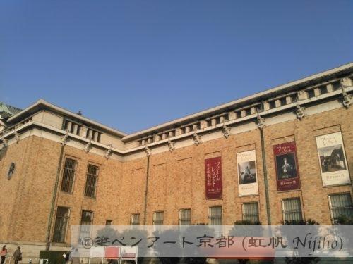 夕日が当たる京都市美術館外壁とフェルメールとレンブラント展のポスター